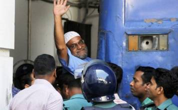 Jamaat-e-Islami party leader, Mir Quasem Ali waves his hand as he enters a van at the International Crimes Tribunal court in Dhaka on November 2, 2014. PHOTO: AFP