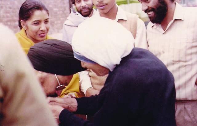 Mrs. Gurdarshan Kaur watches as her husband Prof. Saluja as he kisses the hands of Mother Teresa.