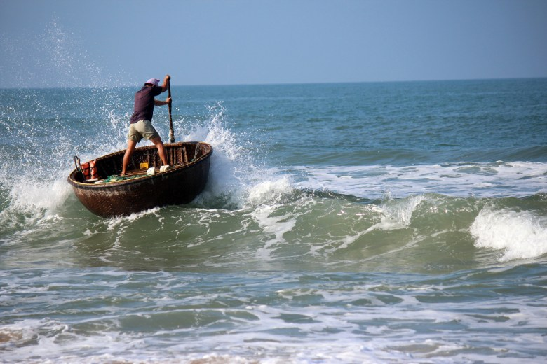 The motion of the fisherman navigating out through the waves in the traditional woven bamboo basket boats adds to the image
