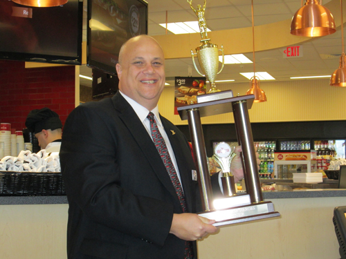 Photo by Ron Leir Scott Kent, Wawa area store manager, displays trophy wonby Kearny FMBA for hoagie contest