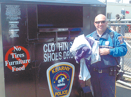 Photo courtesy KPD Officer Damon Pein makes a donation at the new KPD clothing/shoes collection bin off Bergen Ave.