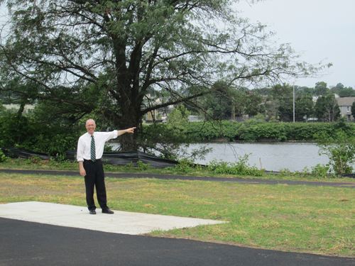 Photo by Ron Leir Mayor Alberto Santos gestures to a section of the future Frank Cardoza Park and the Passaic River just beyond.