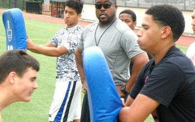 Photo by Jim Hague New Harrison head football coach Rich Glover Jr. (c.) leads his new team through a blocking drill during a workout last week.