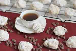 Cup of espresso surrounded by dusted Pecan Meltaways and chocolate chips