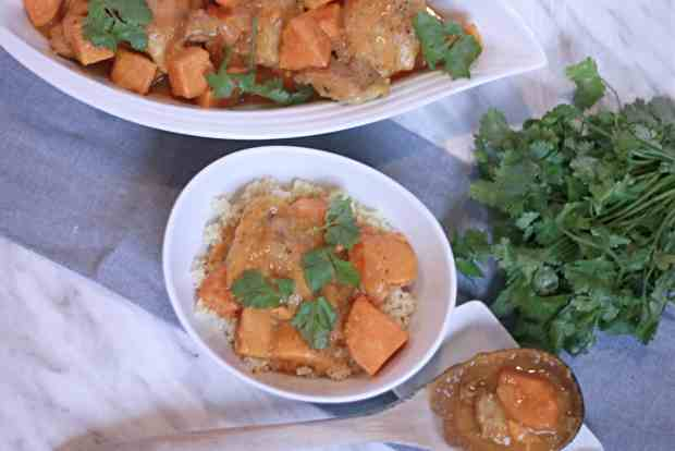Moroccan Chicken Stew in large white serving bowl with fresh herbs