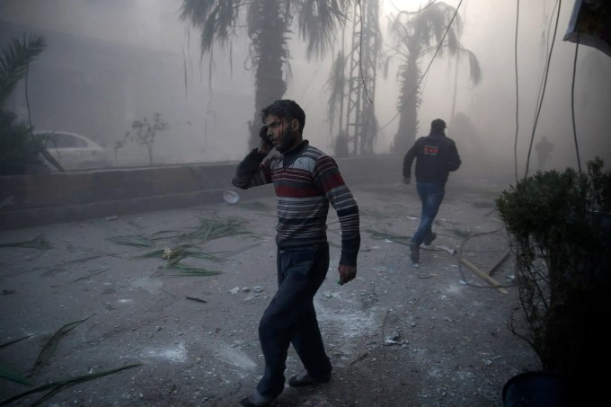A wounded man walks out of a dust cloud following reported airstrikes in the town of Hamouria in the eastern Ghouta region, a rebel stronghold east of the Syrian capital Damascus, on December 9, 2015. The Syrian Observatory for Human Rights reported at least 11 civilians, including four children, were killed in strikes on the town of Hamouria, but said it was unclear if they were carried out by Russian or regime aircraft. AFP PHOTO / SAMEER AL-DOUMY