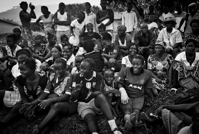 Bandu Turay, second to top row, fourth from right, watches her son Erison, not pictured, play soccer as others cheer for the Ebola Survivor's Soccer Club, on a field near their house, in the city of Kenema, 190 miles east of the capital Freetown, Sierra Leone, Tuesday, April 21, 2015. Last year, 38 members of Erison's family died from the deadly Ebola virus, which has killed over 11,000 across West Africa. Erison founded the Ebola Survivor's Soccer Club as a support network for survivors and a means to battle negative stigmas in the community. (Photo Credit/Tara Todras-Whitehill for the New York Times)