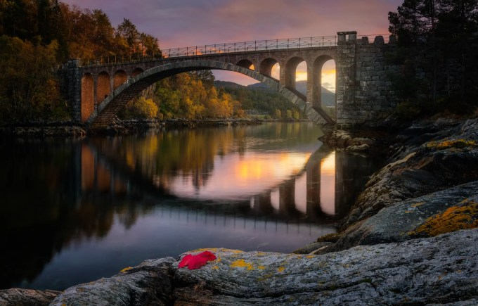 """500px Photo ID: 125762115 - I didnt really want to call it Skodje Brua, and it feels like something out of a fairytale, but couldnt think of a special one that it fit, so i thought I would leave it up to your imagination and decide which fairytale or bridge it reminds you of. For those that follow my profile I already posted a photo from here, but it is the other bridge as this one is part of two right after one another. The great grandfather of one of my friends was one of the ones that helped build this bridge and as a kid this was the regular bridge we used to get to the city. SCARY, expecially in the winter, you dont have a good view if there is another car coming on the other bridge as you go on. and there is pretty much place for one car as a time. and parts of it are on a slope, combined with ice can be scary. But now there is a large bridge just a hundred or two meters from this one that you can zoom by. While walking down the path down to here I noticed a 5 point leaf with great red colors, and so I took it along to put specifically in my composition in the name of Autumn. I did a bit more editing than im used to. but as a disclaimer most of the magical feeling is by making a HDR and darkening the whole as well as specific areas. and that was enough for most. I should have taken one more exposure for the sunlight but realised I didnt, so I had to paint out a bit of the white in the sky. added a bit of warmth to the sunset as well as selective vignetting. as well as about 15 images were used to make this. combined with HDR, long exposures, and Focus stacking to get the desired effect. especially when working with such small details. I dont know why, I love autumn and all the colors, But I dont feel as inspired to do nature photography and Feel more like """"Oh I guess I should take some photos of the season."""" I like my results a lot there is something about it. cant quite wrap my brain around it. I hope yall enjoy it =D Feel Free to Share =D"""