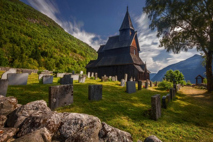"""500px Photo ID: 91716599 - One shot I love, that i re-edited for a stronger composition and mood. of course is best in large and black background Information about the church is at Which I copy and pasted the description from you to read if you wished to read. http://www.stavechurch.com/en/urnes/ you can follow me here or at https://www.facebook.com/artiwangroot Like, Favorite, Comment, Share, Enjoy! =D """"A stave church has been built three times on the same site here at Orneset. A hundred years would pass between the first and the third, the one we can visit today. The timber was felled in the years 1129-1130. On the long northern wall, original decorated sections from the demolished church have been used: the portal, wall planks and a corner post. The decorated gables from the same church are now covered to prevent wear and tear. The stave churches are Norway's unique contribution to the world's cultural heritage. Most were built between approx. 1130 and 1350, when the Black Death brought all new building to an end. Similar churches existed elsewhere in Europe, but only the Norwegian ones have survived. Of the original approx. 1,000 churches, 28 remain. Urnes stave church is the eldest and most highly decorated of them. In 1979 it was included on UNESCO's World Heritage List. In this description, we delve back to the time when the church was built, approx. 20 years before catholic Norway became a separate province under the Pope in Rome. Ownership of Urnes stave church was transferred to the Society for the Preservation of Norwegian Ancient Monuments in 1880. The society's logo is taken from the carved capitals inside the church."""""""