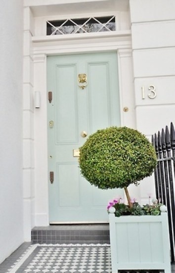 Light blue front door and boxwoods