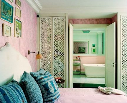 lattice pattern on shelving creates an open space in this bedroom via Lonny