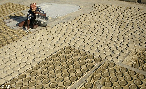 """A woman """"cooking"""" mud pies in Haiti. The pies are made from clay, salt, oil and water."""