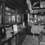 """This drugstore features a hanging display (upper right) of the June 3, 1922, number of """"Argosy All–Story Weekly,"""" featuring """"His Third Master"""" by Max Brand."""