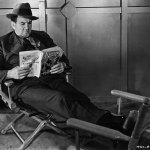 """Character actor Tom Kennedy reads a tattered issue of """"Complete Detective Novel Magazine"""" (February 1929) while filming """"The Fall Guy"""" for RKO Pictures. The movie was released June 15, 1930, so it's uncertain if the photo was taken in 1929 or early '30. (Courtesy of Ed Hulse of Murania Press)"""