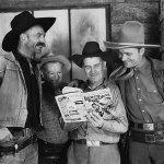 """Screenwriter Robert Emmett Tansey holds a copy of the second March 1937 number of """"Ranch Romances"""" in this photo with Hank Worden, left; an unidentified man; and Tex Ritter, right. It's a publicity photo from the 1937 Grand National Pictures' """"Hittin' the Trail."""" (Thanks to David Lee Smith for discovering the photo, and Ed Hulse for providing the names and title of the movie.)"""