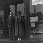 """A man and woman pose in front of a store, where displayed in the right window are copies of """"Dare-Devil Aces"""" (June 1938), """"Lone Eagle"""" (June 1938) and """"Knockout Magazine"""" (June-July 1938)."""