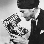 """Actor Kenneth Duncan, dressed as Ram Singh from the 1938 film serial """"The Spider's Web,"""" poses with the October 1938 number of """"The Spider"""" pulp in this publicity photo."""