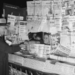 """At first, there appear to be no pulp magazines for sale at the newsstand displaying a variety of foreign newspapers dated mid-August 1941. But, if you look below the """"Friday"""" magazine, you'll see dozens of pulp magazines displayed spines up."""