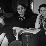 """While the women pose for a photo, the man on the sofa is engrossed in the January 1942 issue of """"Amazing Stories."""""""
