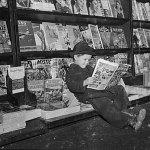 A kid reads a comic book at this newsstand in March 1942, while a few pulps are on display behind him.