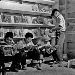 """Four youth — confined to the War Relocation Authority center in Newel, Calif. — enjoy the latest comic books available at the newsstand in July 1942. In the upper right, issues of """"Fantastic Adventures"""" (August 1942) and """"Wild West Weekly"""" (June 20, 1942) await sale."""