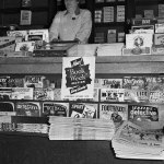 """This newsstand has for sale a number of November and winter 1942 issues of pulps along its lower shelves: """"Exciting Storts,"""" """"Exciting Mystery,"""" """"Fight Stories,"""" """"Detective Story,"""" """"The Shadow,"""" """"Short Stories,"""" """"West"""" and more."""