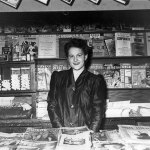 """A young woman stands in a news stand in early 1943. In the upper left is the type-heavy cover of """"Unknown Worlds"""" (February 1943), as is part of the cover of """"Astounding Science-Fiction"""" (March 1943)."""