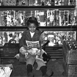 A young girl in Pittsburgh, Pa., reads a comic book, while pulps from March 1947 await sale on a rack nearby.