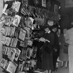 """Actress Betsy Drake poses at a so-called """"newsstand"""" in this Warner Bros. publicity photo. It's sometime after 1949, since there is a """"New Yorker"""" cover dated July 1949. Otherwise, this stand is chock-a-block with magazines, both real and fictitious, from a variety of dates — but no pulps. There is a neat poster for The Shadow at the top."""