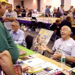 Ron Fortier, seated right, discusses his Captain Hazzard book as Don Hutchison, author of The Great Pulp Heroes, sits beside him at a dealer's table.