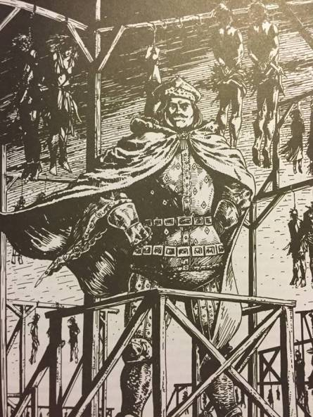 The Prince standing proudly on a gibbet with bodies hanging behind him