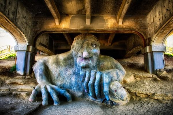 The Fremont troll, a large sculpture under the fremont bridge. He has long hair and a beard, and has a VW Beetle clutched in his hand. He looks like he's crawling out of the ground towards you