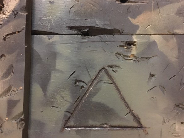 Top of a crate with a triangle carved into it