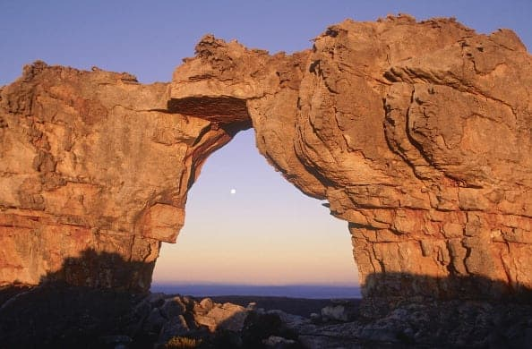 South Africa, Northern Cape, Cederberg, The Wolfberg Arch rock formation framing the rising moon (Photo by: Eye Ubiquitous/UIG via Getty Images)