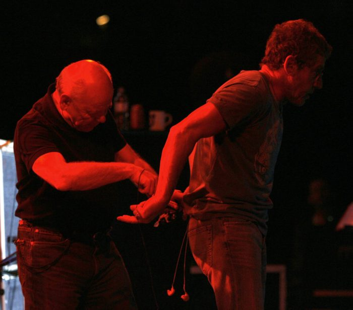 The Who's onstage sound engineer Bob Pridden adjusts Roger Daltrey's inner ear monitors during The Who's performance at Indian Wells Tennis Stadium, Palm Springs, CA, on November 11, 2006.