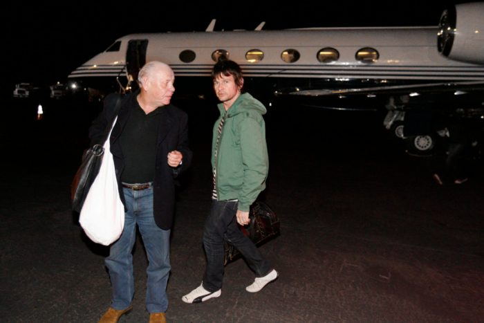 The Who's onstage sound engineer Bob Pridden and drummer Zak Starkey head to their cars after exiting their plane in Denver, CO.