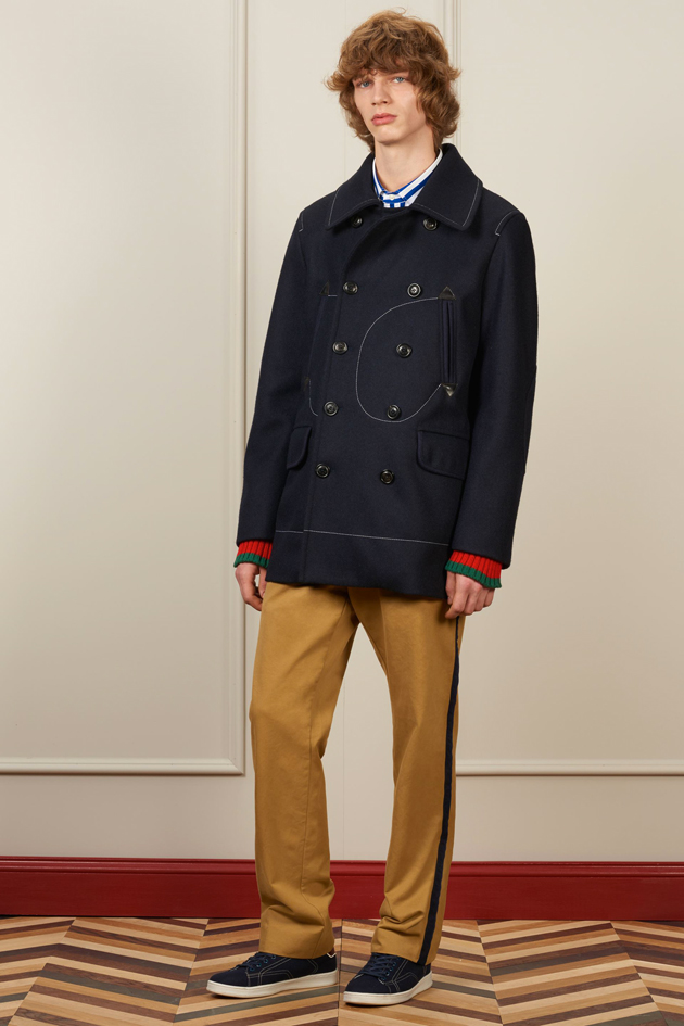 Tommy Hilfiger FW16 lookbook, model is wearing a navy sailor-inspired peacoat, and a pair of camel trousers with trainers