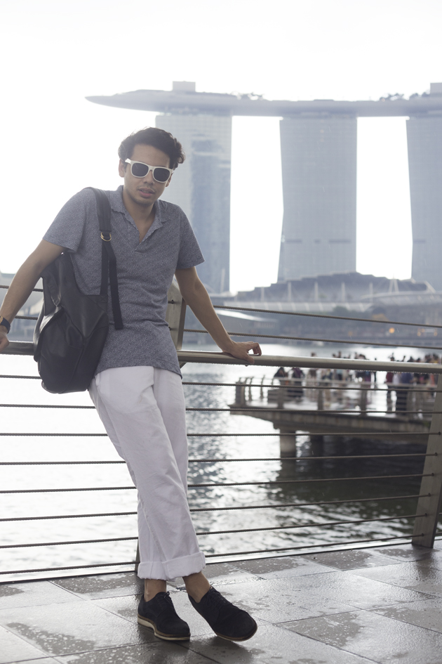 Ronan Summers poses by the Merlion statue, with the Marina Bay Sands in the background, wearing Orlebar Brown SS16 collection