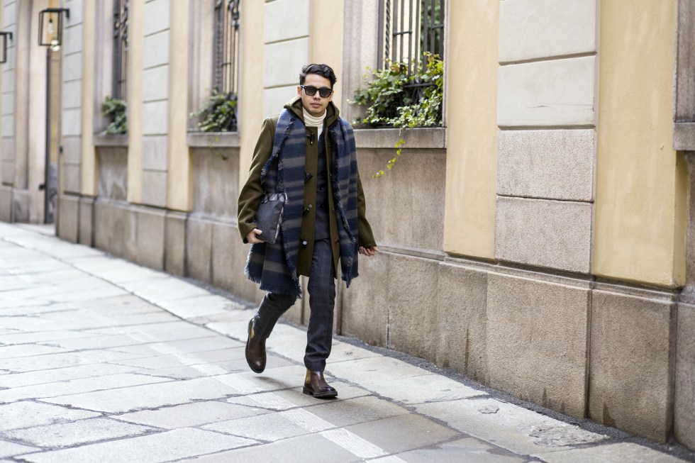 Menswear influencer Ronan Summers is in Milan for fashion week men's and is wearing a Gloverall khaki toggle coat and double breasted suit