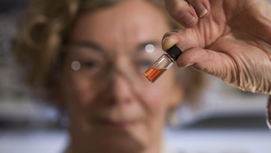 Biochemistry Lab Manager Janet Hope from the ANU Research School of Earth Sciences holds a vial of pink coloured porphyrins representing the oldest intact pigments in the world. Image credit: Australian National University