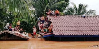 People sat on roof of flooded house in Laos