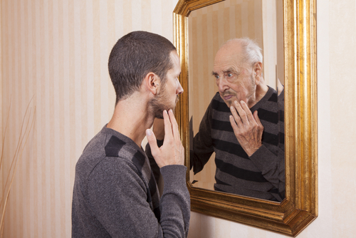 young man looking at an older himself in the mirror   shutterstock