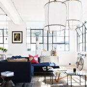 Sun-filled living room with over-sized lantern pendants and contemporary blue sectional.
