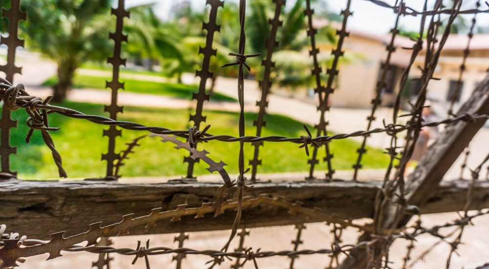 Looking out from barbed wire at the Tuol Sleng Museum of Genocide