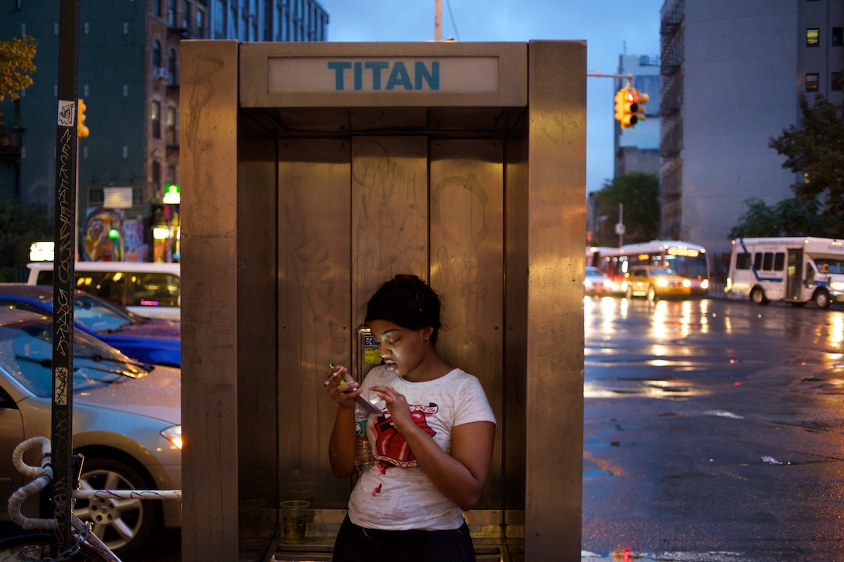 A young woman uses a cell phone in a phone booth on the Lower East Side of New York City.  Photo: Tom Pietrasik New York City, USA  October 15th 2014