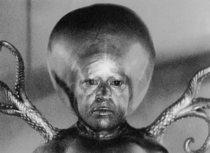 A view of the Martian Intelligence from Invaders from Mars.  Actress Luce Potter, a midget, played the Martian Intelligence in close-ups.  Without the benefit of dialogue, Ms. Potter's eyes are the only means of expressively conveying the strange aloofness of this otherworldly character.  The brothers Howard and Theodore Lydecker molded the brontocephalic dome of the creature and its atrophied body in rubber.  The tentacles were operated by grips with wires positioned beyond the range of the camera and a special gold metallic make up was formulated by cosmetics expert Anatole Robbins and applied by make up artist Gene Hibbs. Click to enlarge.