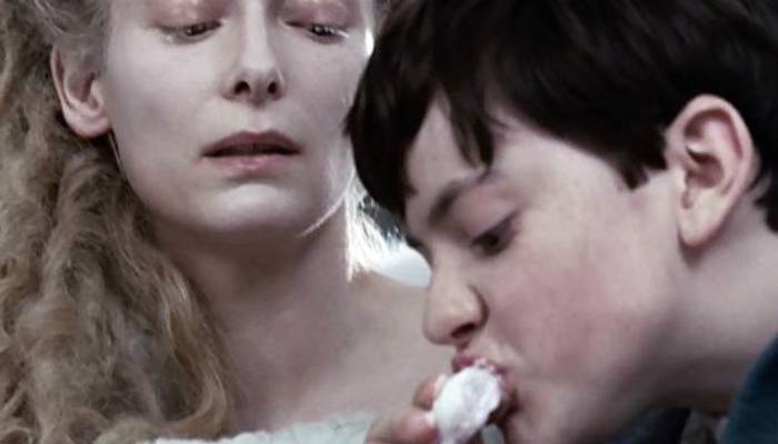Edmund eats Turkish Delight under the watchful eye of the White Witch