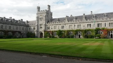 green grass in the quad at University College Cork with university buildings in the background