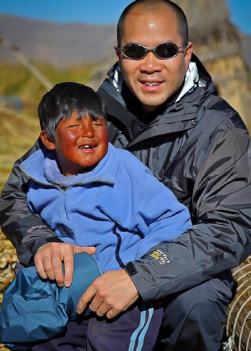 With friendly Uros boy on Floating Island of the Uros, Lake Titicaca, Peru