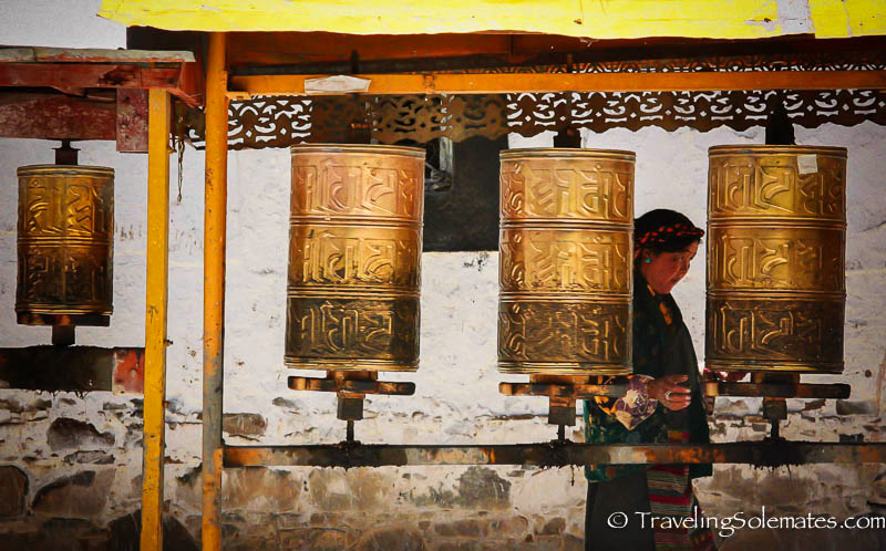 A woman circumambulating around a series of prayer wheels in Tashilhunpo, Tibet